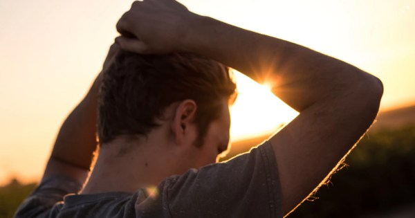 Man gripping his hair in the sunlight.