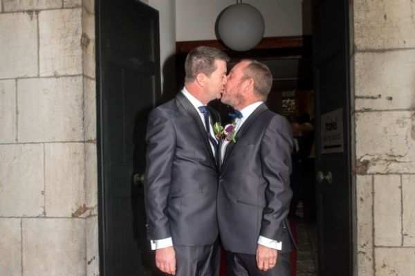 TD Jerry Buttimer at his wedding to his husband, kissing him in front of the door to the venue.