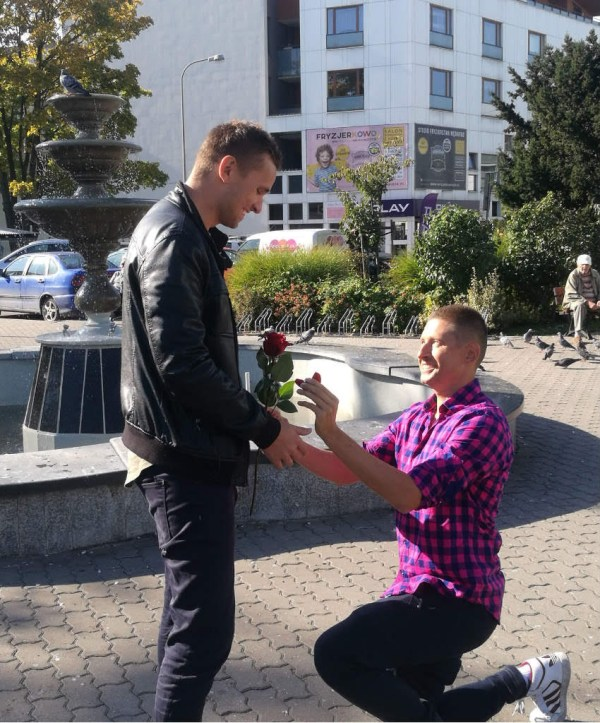 David proposes to Jakub in front of a fountain in a Polish town.
