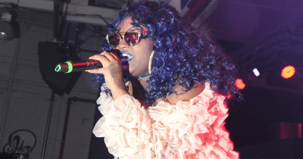 CupcakKe performing on stage wearing a pink jacket and sun glasses