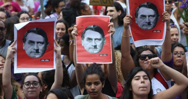 A protest in Brazil, people hold a sign which compares Bolsonaro to Hitler