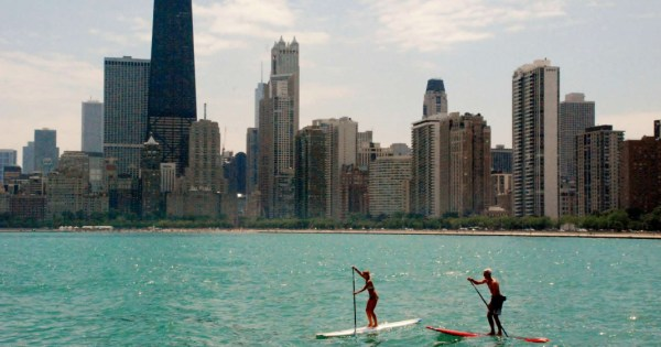 Two people paddleboard along the Chicago River.