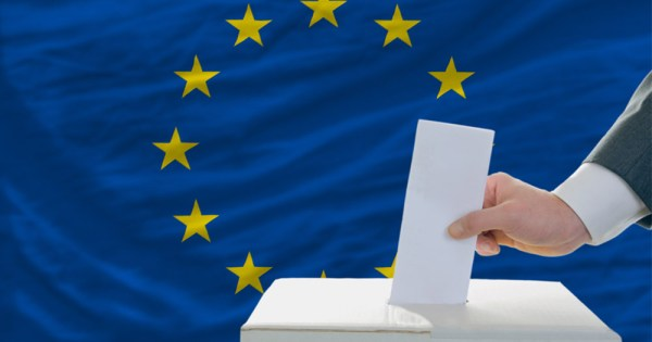 A hand places a paper vote into a ballot box backed by the European flag