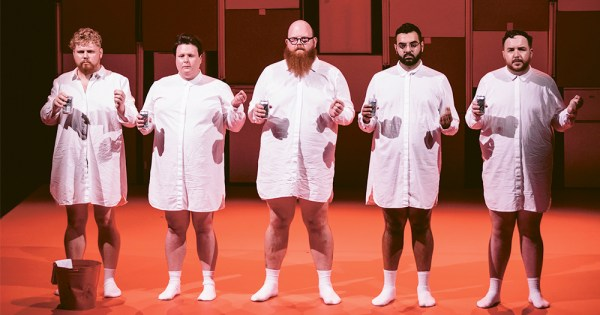 An image from the show Fat Blokes featuring five men in long white shirts standing on stage