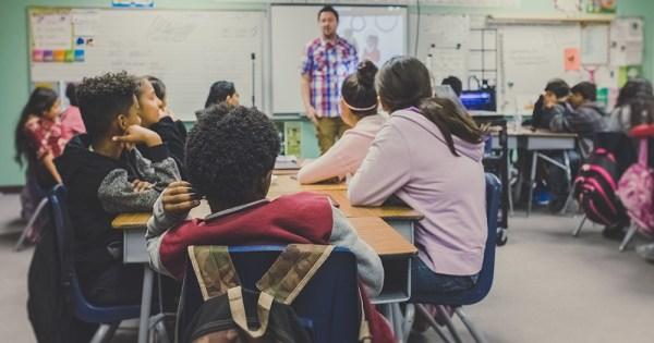 A teacher teaching a class full of students