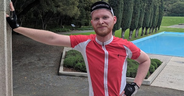Conor Kavanagh wearing cycling gear leaning against a wall, promoting his upcoming cycling for AIDS foundation
