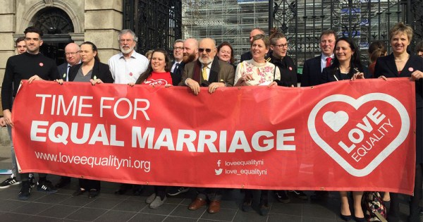 """Love Equality members from Northern Ireland holding up red banner reading: '""""time for equal marriage"""" before briefing the Oireachtas"""