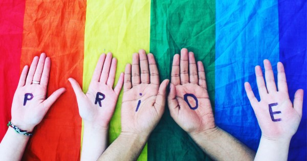 A rainbow flag and 5 hands. Each hand contains a letter from the word PRIDE. This is the cover of the new magazine GLUEPOT