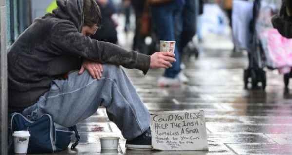 homeless man begging on the street holding a cup