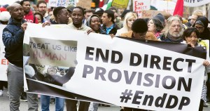 A group of protesters holding a sign that reads: end direct provision