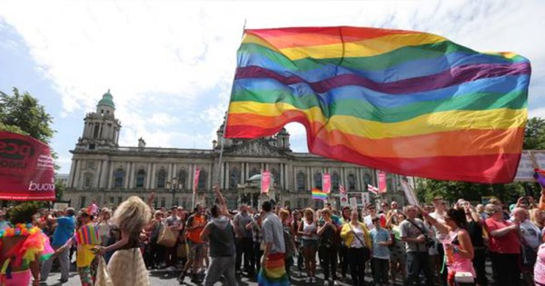 rainbow flag waves in front of city call in Pride in Belfast