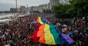 crowd in Brazil holds up massive rainbow flag