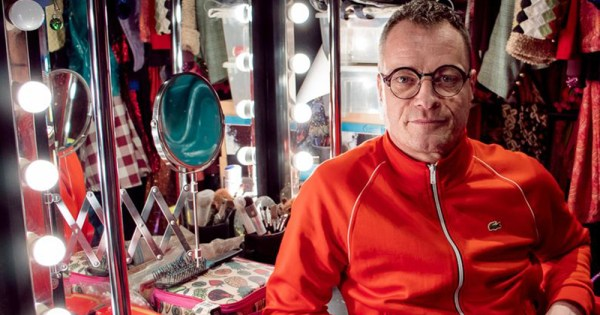 Rory O'Neill sitting in front of a mirror in his dressing room with clothes hanging all around