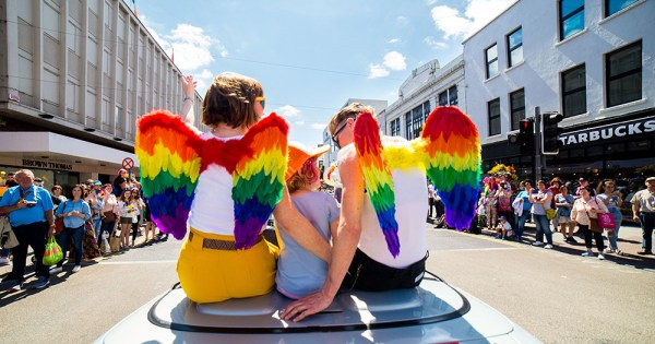 moms in angel wings sit on pride parade car with son