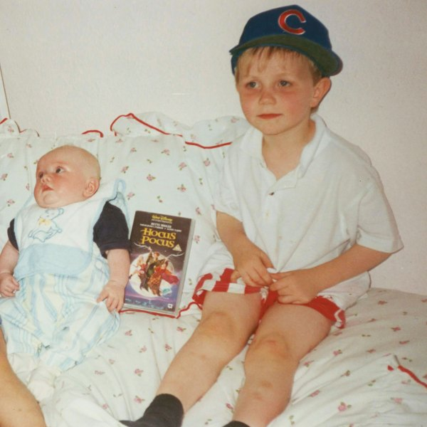 Family photo of a new born baby on a bed, his brother beside him. A VHS tape between them