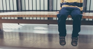 A child sitting on a bench with their feet hanging down