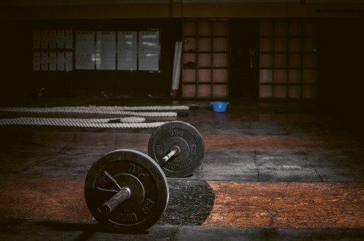 A dark gym hall, a huge barbell on the floor