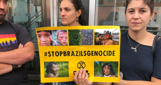Woman holding a sign saying hshtag Stop Brazils Genocide as part of Extinction Rebellion protest