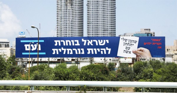 Political ads with Hebrew writing on a billboard by a highway, skyscrapers behind