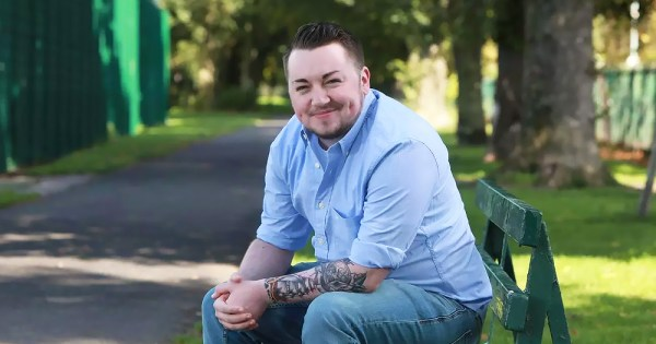 Jack Murphy, a young trans man with a beard, smiles at the camera while sitting on a park bench