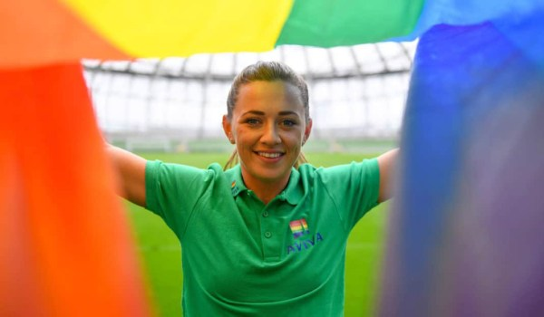 Katie McCabe holding up a rainbow pride flag in Aviva stadium