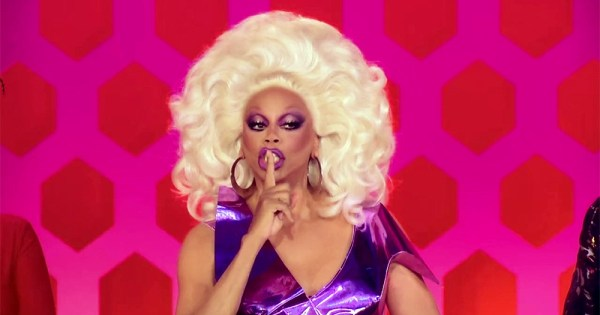 RuPaul, in full drag, makes a shushing gesture to the camera