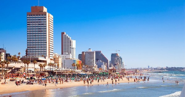 A beach in Tel Aviv on a sunny day, skyscrapers in the background