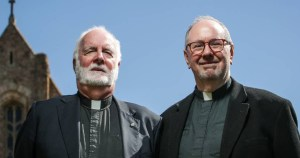 Married gay priests in their 50s standing outside a church