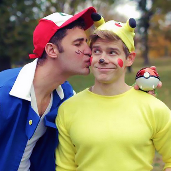 Two men dressed as Ash and Pikachu, one is kissing the other one