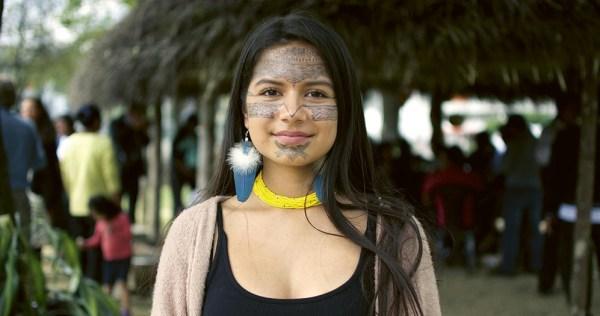 A young Ecuadorian climate crisis activist with tribal designs on her face