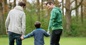 Two men hold the hands of a child as they enjoy a family walk in the woods. The are wearing green, blue and white sweaters repectively.