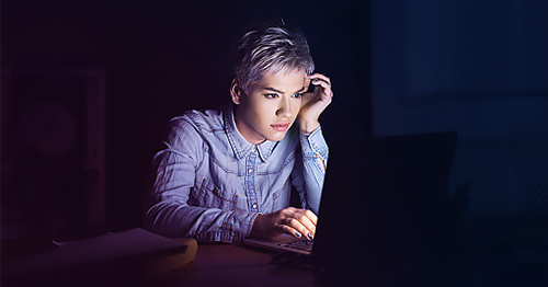 Woman with short hair and a denim shirt looking at digital content on her laptop in a dark room.