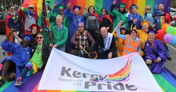 The Kerry Pride team all in rainbow colours with a huge rainbow flag behind them, holding a huge banner
