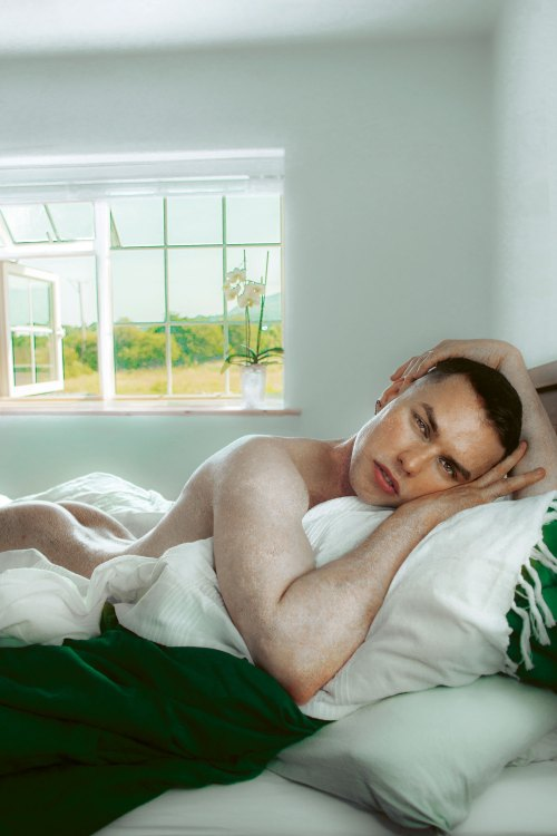 A naked man laying on a bed, behind him a window