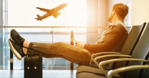 Man in an airport, his feet resting on his case, looking out the window at a plane taking off