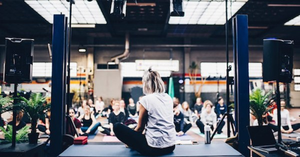 Woman sitting cross legged in front of audience as part of Thrive Festival 2020