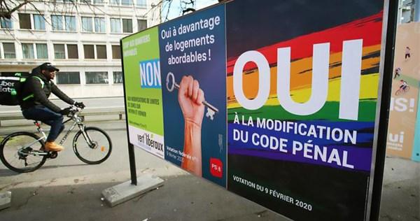 Man cycles past referendum posters. Switzerland discrimination