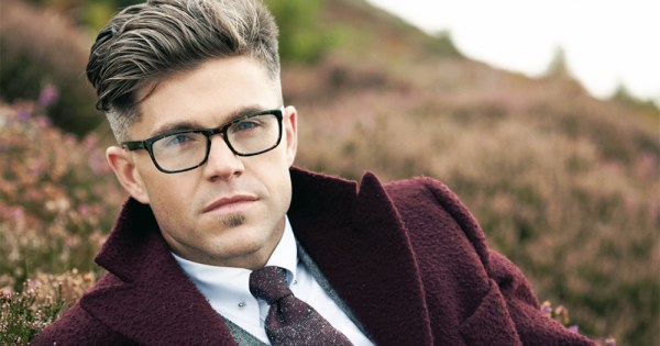 Close-up of Darren Kennedy wearing a burgundy coat and glasses