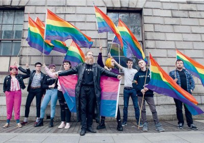 Jon Hanna with protesters holding a bisexual flag