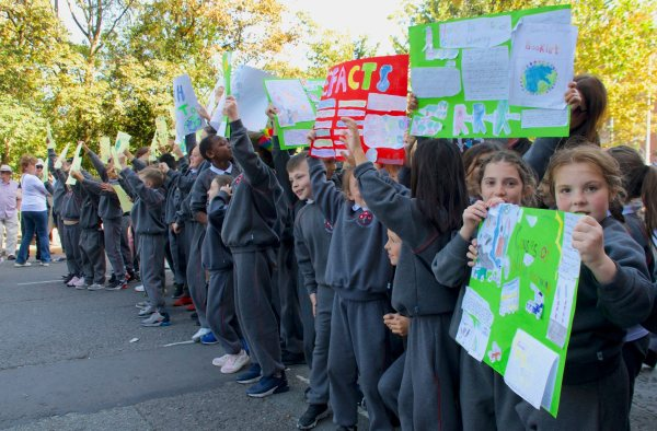 A group of very young schoolchildren holding homemade signs to protest climate change