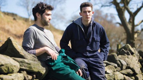 Two men dressed in work clothes lean against a stone wall in the countryside