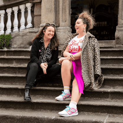 Two laughing hipster women sits on the steps leading up to a building