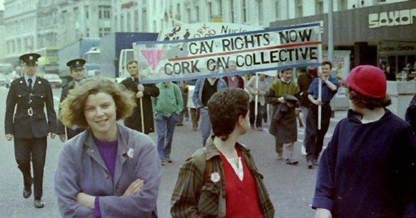 An old photo of the Cork Gay Collective holding a banner walking down a street accompanied by policemen while three women look on