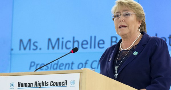 UN High Commissioner for Human Rights, Michelle Bachelet speaking at a podium, issuing a warning to not attack the LGBT+ community under COVID-19 emergency powers