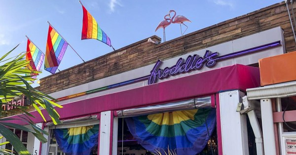 The exterior of a gay bar with flamingos and rainbow flags