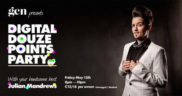 A drag king with slicked back hair and a white tuxedo stands against dark background