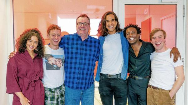 One woman and five men smilingly pose for a photo