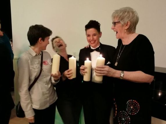 A group of four women holding candles and laughing