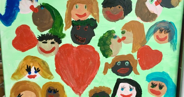 A child's painting of lots of different faces with a big love heart in the middle