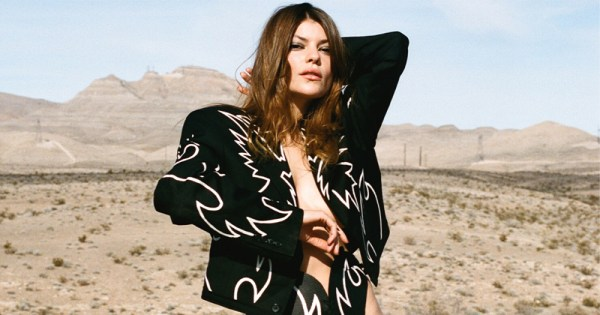 A long haired woman in a stylish jacket stands in an American desert